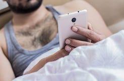 Закройте вверх молодых пальцев рук мужчины работая в кровати на sms мобильного телефона печатая на клавиатуре Стоковые Изображения