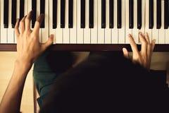 Закройте вверх молодых рук мальчика, играющ рояль винтажный фильтр тона Стоковое Изображение