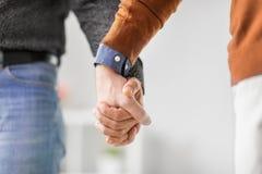 Закройте вверх мужских пар гомосексуалиста держа руки Стоковые Фотографии RF