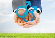 Закройте вверх мужских пар гомосексуалиста держа символ рода Стоковая Фотография RF