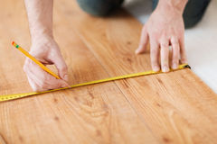 Закройте вверх мужских рук измеряя деревянный настил Стоковые Изображения RF