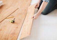 Закройте вверх мужских рук intalling деревянный настил Стоковые Фото