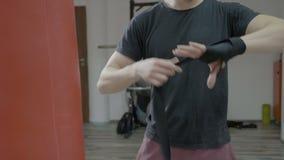 Закройте вверх мужского боксера оборачивая повязки бокса вокруг его рук в спортзале тренировки - сток-видео