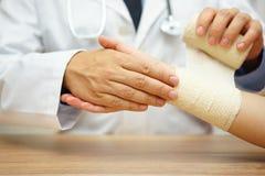 Закройте вверх мужского доктора перевязывая женскую руку стоковые фото