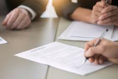 Закройте вверх мужской руки кладя подпись в контракт Стоковое Фото