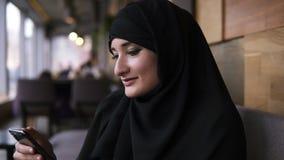 Закройте вверх мусульманской женщины в кафе используя ее смартфон, беседовать онлайн с друзьями или средства массовой информации  видеоматериал