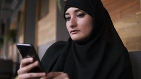 Закройте вверх мусульманской женщины с макияжем в кафе используя ее смартфон, беседовать онлайн с друзьями или средства массовой  акции видеоматериалы