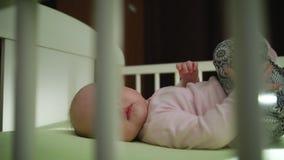 Закройте вверх младенческого младенца кладя в ноги шпаргалки вверх по движению акции видеоматериалы