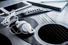 Закройте вверх наушника с мобильным телефоном на гитаре Стоковые Изображения