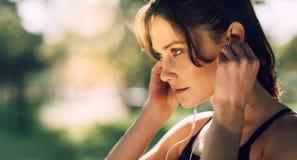 Закройте вверх наушников спортсменки нося outdoors Женщина слушая к музыке во время разминки стоковое изображение rf