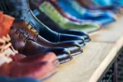 Закройте вверх на ботинках людей кожаных в строке Стоковое фото RF
