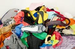 Закройте вверх на большой куче одежд и аксессуаров брошенных на том основании стоковые изображения rf