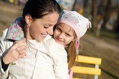 Закройте вверх на иметь потеху играя совместно красивую маленькую девочку с ее матерью весной или парк осени outdoors копирует ко Стоковые Фотографии RF