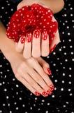 Закройте вверх на красивых женских руках с милым красным маникюром с белыми точками. Стоковое фото RF