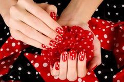 Закройте вверх на красивых женских руках с милым красным маникюром с белыми точками. Стоковое Изображение