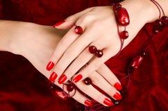 Закройте вверх на красивых женских руках с сексуальным красным маникюром. Стоковая Фотография RF