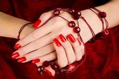 Закройте вверх на красивых женских руках с сексуальным красным маникюром. Стоковое Изображение