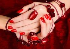 Закройте вверх на красивых женских руках с сексуальным красным маникюром. Стоковые Фото