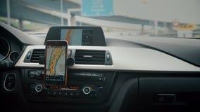 Закройте вверх на положении отслеживая корабля навигации экрана и направьте пока управляющ на дороге Навигация GPS на smartphone акции видеоматериалы