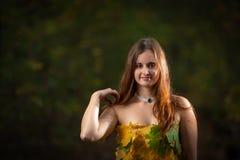 Закройте вверх на привлекательной маленькой девочке с платьем длинных волос нося сделанным из красочных листьев в лесе осени стоковое фото rf