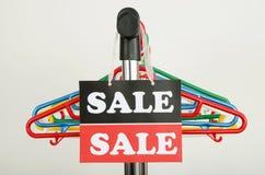 Закройте вверх на пустых вешалках и большом знаке продажи Стоковые Фотографии RF