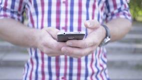 Закройте вверх на руках ` s человека просматривая smartphone съемка слайдера видеоматериал