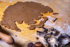 Закройте вверх на тесте пряника и формах, резцах на деревянном столе стоковые фотографии rf