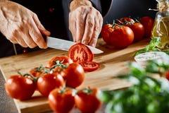 Закройте вверх на человеке отрезая вверх по малым томатам стоковое фото rf