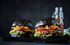 Закройте вверх на черных гамбургерах плюшки Стоковое Изображение