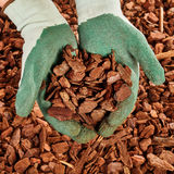 Закройте вверх на gloved руках вполне mulch Стоковые Изображения RF
