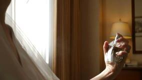 Закройте вверх невесты используя духи на ее день свадьбы на гостиничном номере Благоухание анонимной женщины распыляя в замедленн акции видеоматериалы