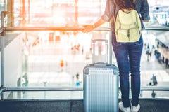 Закройте вверх нижней части тела взятия женского путешественника ждать с полета в возвышенность в терминальном аэропорте Люди и о стоковые фото
