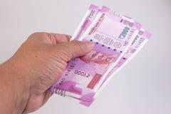 Закройте вверх новой банкноты 2000 рупии на руке человека Махатма Ганди на индейце 2000 банкнот рупии стоковая фотография rf
