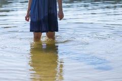 Закройте вверх ног девушки стоя в воде озера Стоковая Фотография