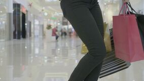 Закройте вверх ног женщины в темных брюках идя и закручивая на мол пока хозяйственные сумки нося в обеих руках - видеоматериал