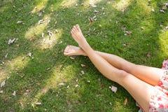Закройте вверх ног пересеченных женщиной лежа на траве Стоковая Фотография
