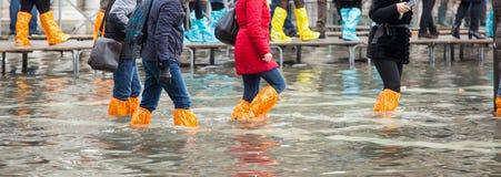 Закройте вверх ног с ботинками должными к приливу в Венеции стоковое изображение