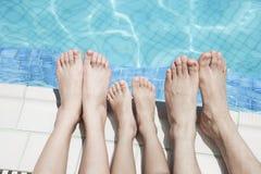 Закройте вверх 3 ног людей стороной бассейна Стоковое Изображение