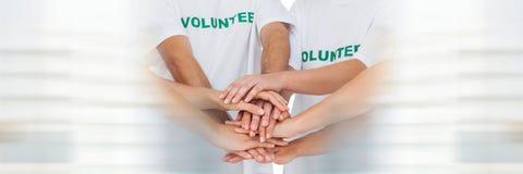 Закройте вверх добровольной команды кладя руки совместно и расплывчатый белый обрамлять стоковое изображение rf