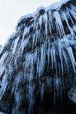 Закройте вверх огромных сосулек на стене утеса горы около водопада Стоковая Фотография