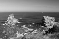 Закройте вверх огромных утесов скалы jumeaux deux в Атлантическом океане с волнами в черно-белом Стоковые Изображения RF