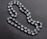 Закройте вверх ожерелья гематита и черного шнура стоковое изображение rf