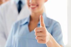 Закройте вверх доктора или медсестры показывая большие пальцы руки Стоковое Изображение