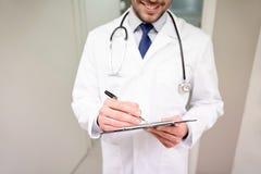 Закройте вверх доктора с доской сзажимом для бумаги на больнице Стоковые Фото