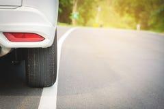 закройте вверх дороги колеса автомобиля на том основании с светом солнца Стоковые Фото