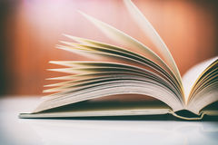 Закройте вверх открытой книги на столе с винтажным фильтром Стоковая Фотография