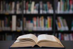 Закройте вверх открытой книги на таблице против полки Стоковые Фотографии RF