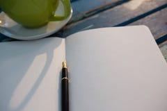 Закройте вверх открытой книги чашкой Стоковое Изображение