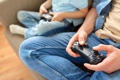 Закройте вверх отца и сына играя видеоигру Стоковые Изображения