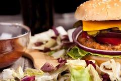 Закройте вверх очень вкусного домашнего сделанного бургера на деревянной плите Стоковое Фото